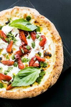Pizza with pepperoni and basil.